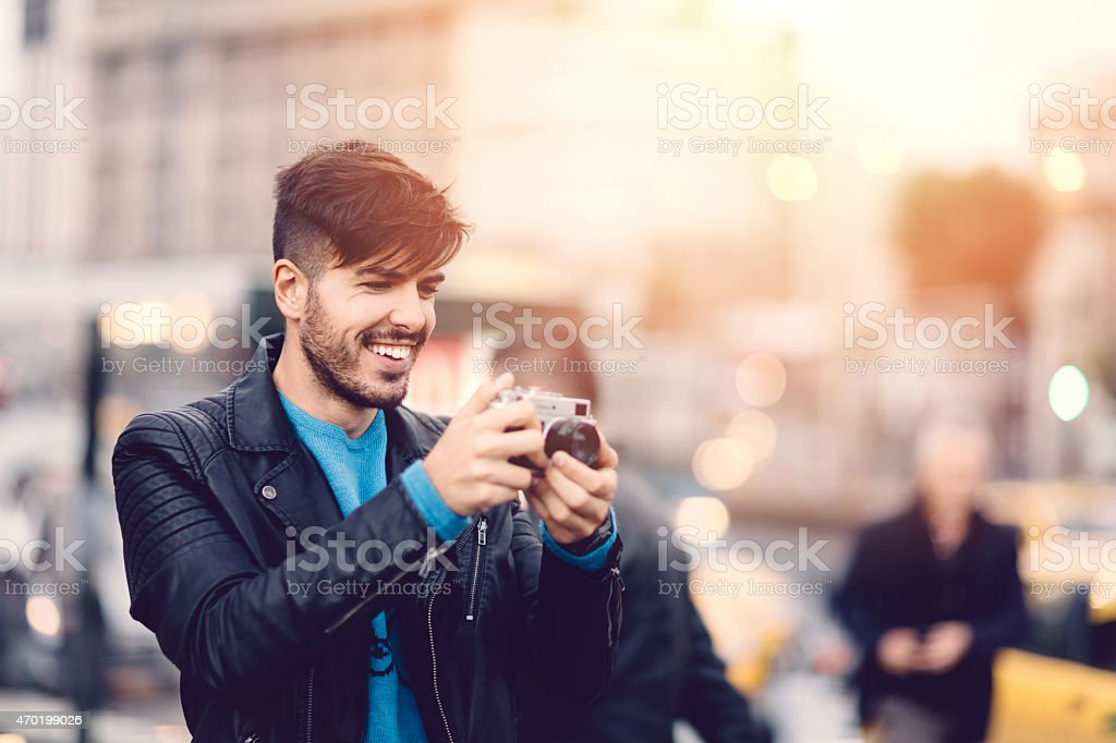 Young man taking a photo with a vintage camera stock photo