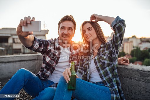 636330566istockphoto Young man taking a selfie with a woman holding hand in her hair and beer in other hand 976566344
