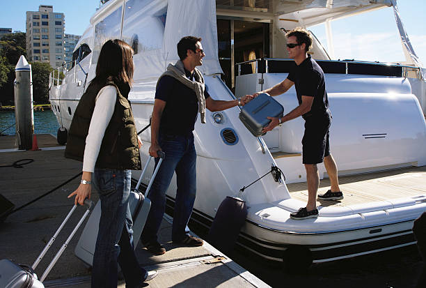Young man taking bags from couple arriving at yacht in marina stock photo