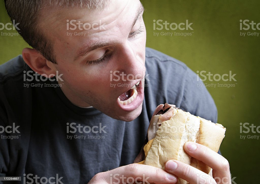 Young Man Taking Big Bite of His Sandwich royalty-free stock photo