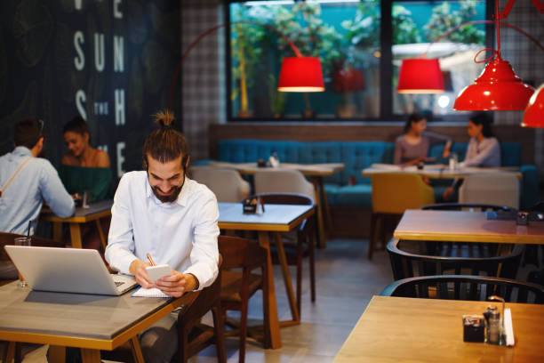 Junger Mann Notizen von einem Laptop im café – Foto