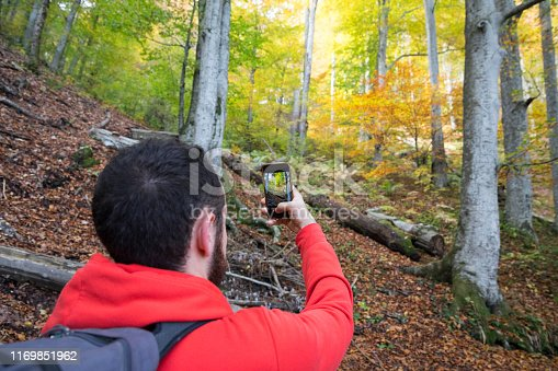 Young man taking photo with his cell phone, of the trees in Plitvice Lakes National Park, Croatia