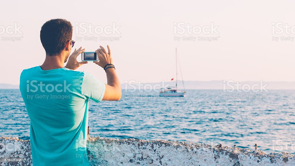 Young man taking photo of yacht with smartphone – Foto