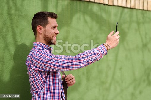 Young man taking photographs with his smart phone in urban background. Guy wearing casual clothes. Lifestyle concept.
