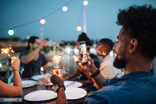 Young man taking picture of sparkler with friends sitting at table during party in evening. People sitting at rooftop enjoying the party.