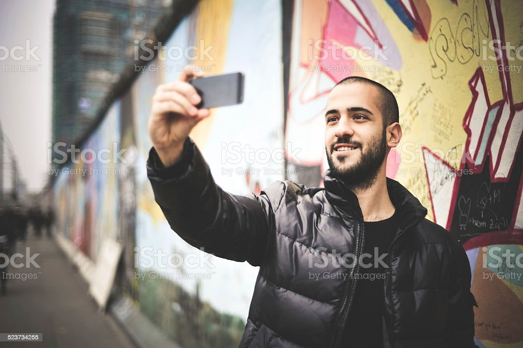 Young Man Taking Selfie In Front Of The Berlin Wall stock photo