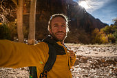 Man taking selfie picture with canyon in Zion national park, USA