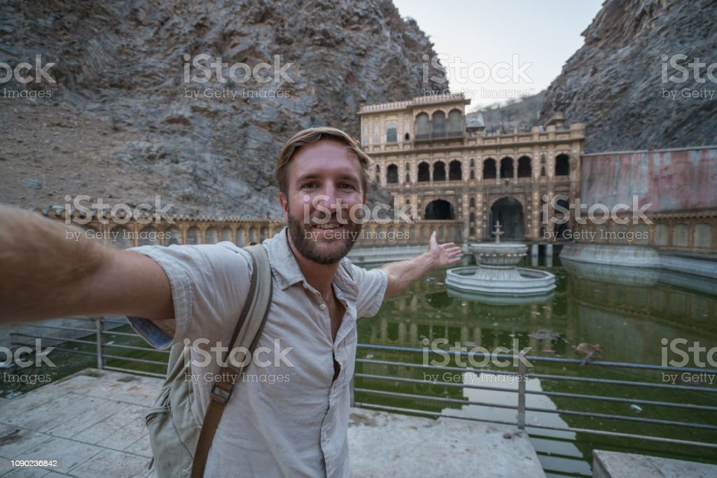 Young man taking selfie portrait inside temple in India -Jaipur,...