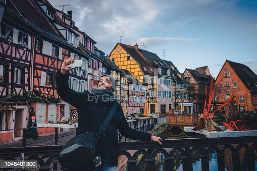 Lovely young tourist male enjoying Christmas, holding smart phone and taking selfie pictures. He is happy, smiling enjoying and looking at camera against water canal and traditional colored houses reflected in river Lauch at Noel time in Little Venise Colmar Haut-Rhin department Alsace France Europe