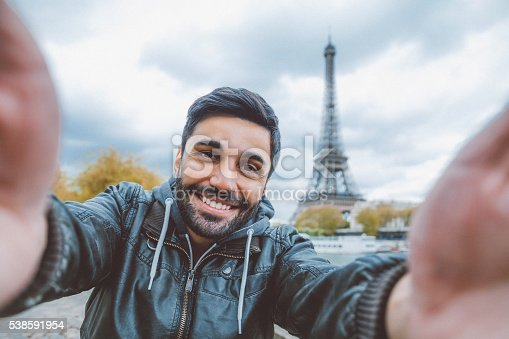 Young middle eastern man holding smart phone and taking selfie pictures. He is happy, smiling enjoying and looking at her camera at coastline of Seine river against Tour Eiffel in Paris, France.