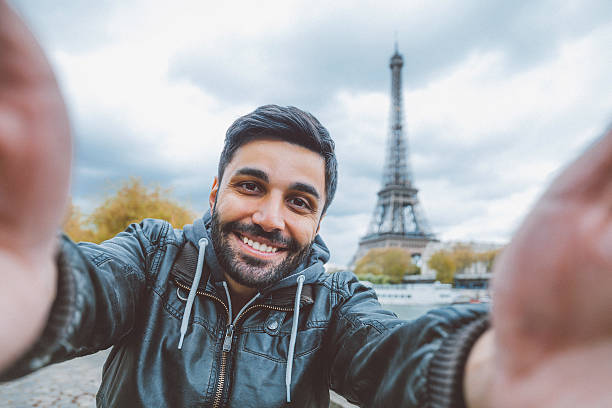 Young man taking selfie with smartphone stock photo