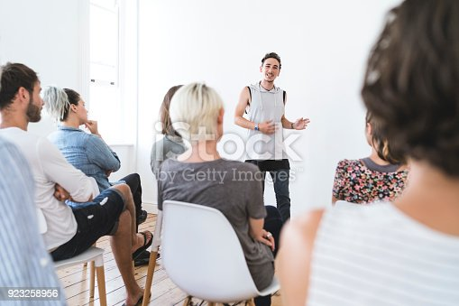 istock Young man talking in group therapy session 923258956