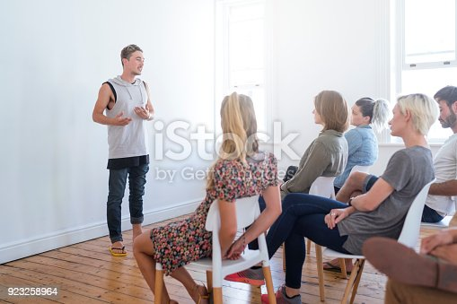 istock Young man talking in group therapy session 923258964