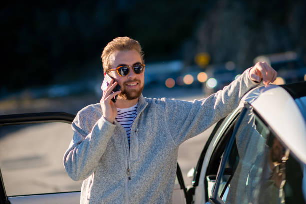 young man talking on his cell phone next to his new hydrogen car - pila a idrogeno foto e immagini stock