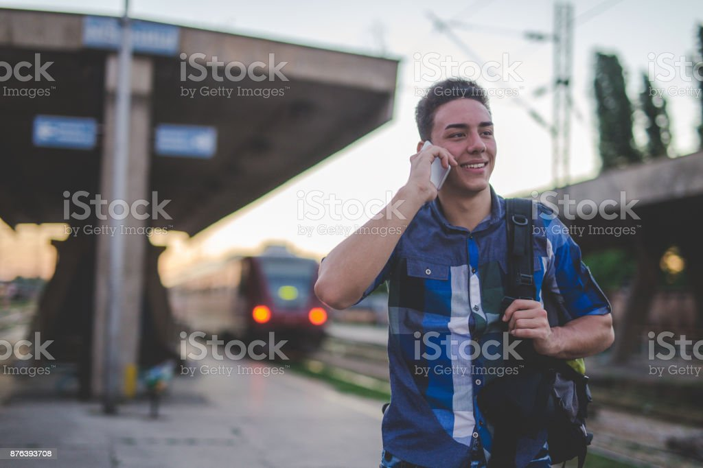 Young man talking on mobile phone at train station stock photo