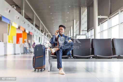 Young african businessman waiting for flight at the airport lounge and talking on mobile phone. Businessman in casuals sitting on chair and waiting for plane.