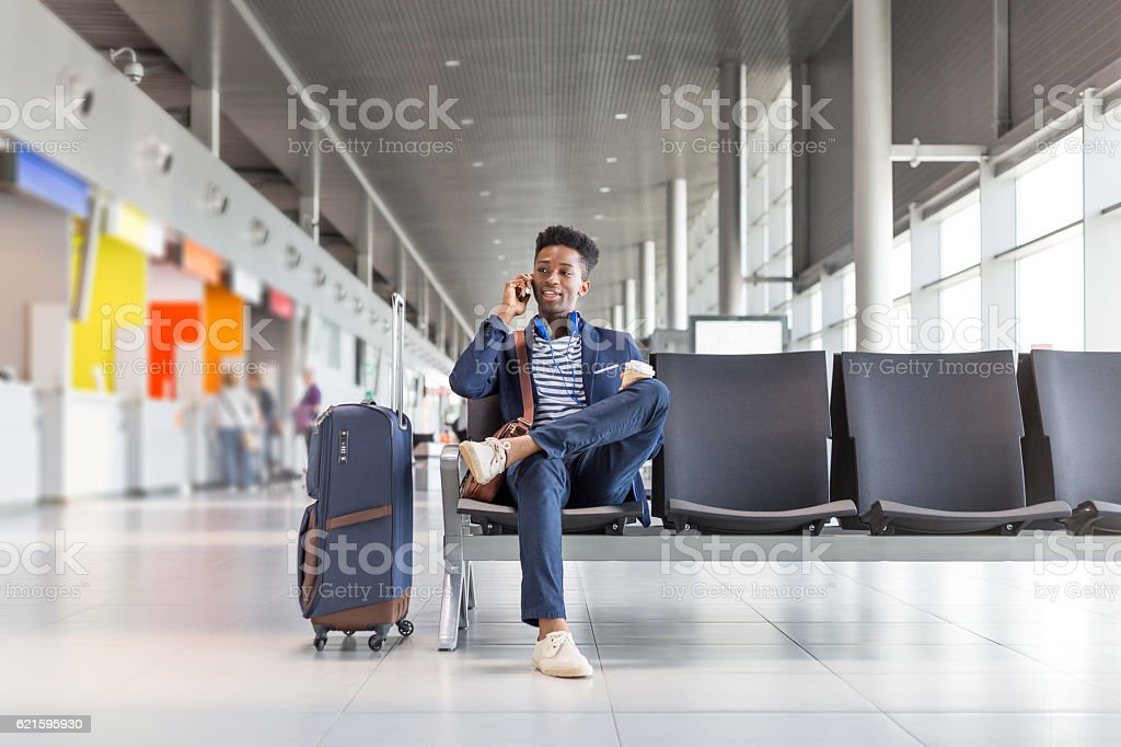 Young man talking on phone at airport lounge stock photo