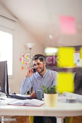 513583458 istock photo Young man talking on phone in office 623513414