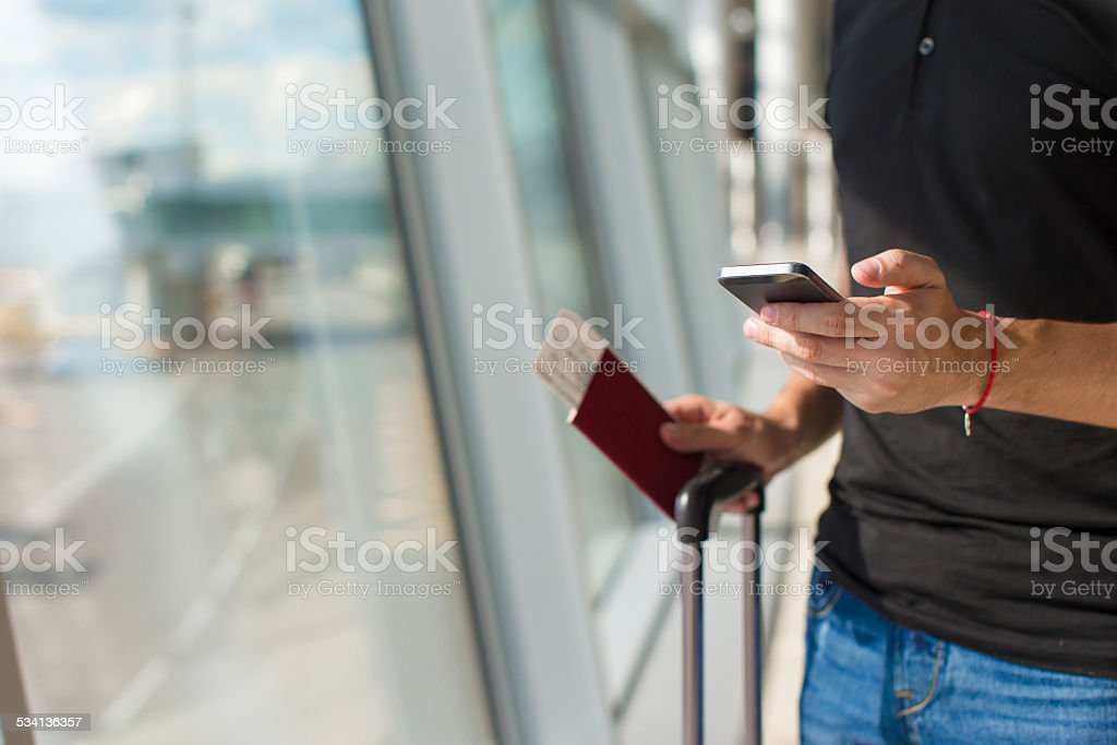 Young man talking on phone inside the airport stock photo