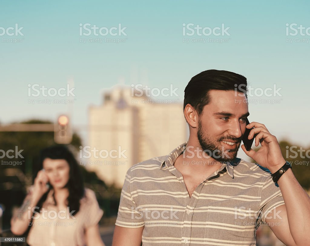 Young man talking on phone outdoor Smiling bearded young man talking on phone outdoor at sunset. Blured woman in the background. Summer time.  2015 Stock Photo