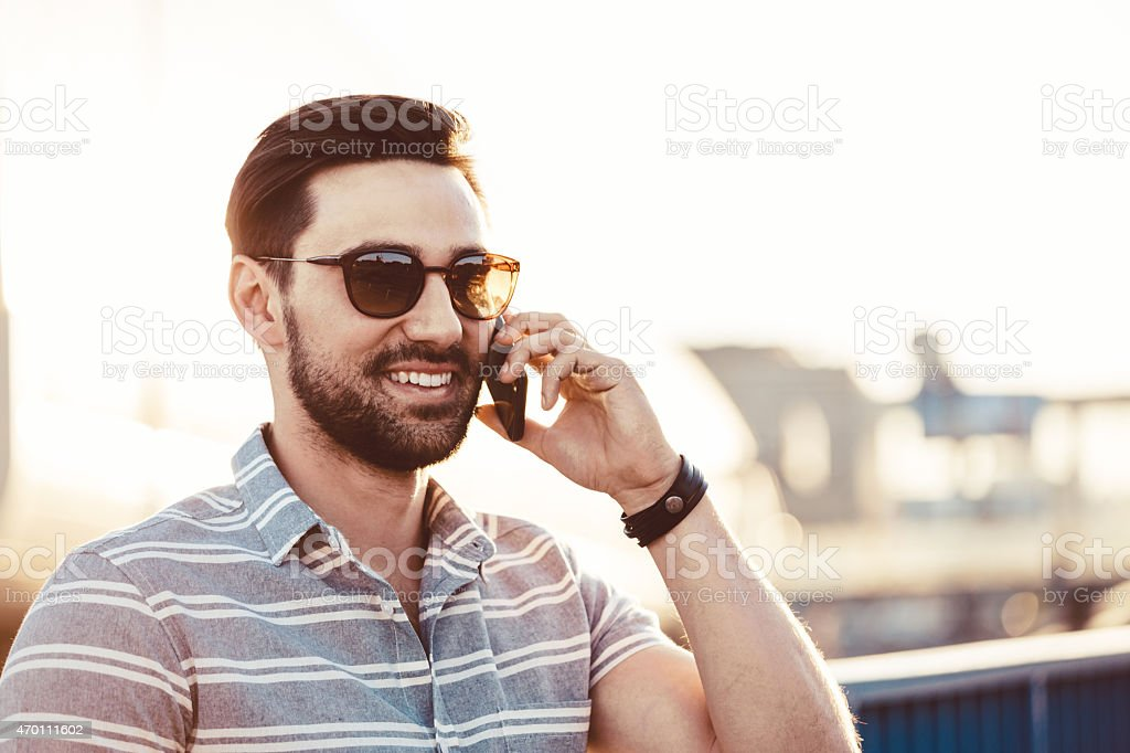 Young man talking on phone outdoor Smiling bearded young man wearing sunglasses talking on phone outdoor at sunset. Summer time.  2015 Stock Photo