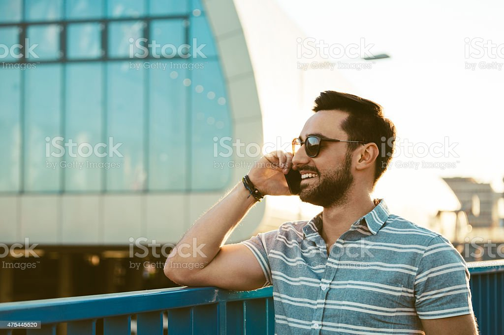 Young man talking on phone outdoor Smiling bearded young man wearing sunglasses talking on phone outdoor at sunset. Summer time.  Adult Stock Photo