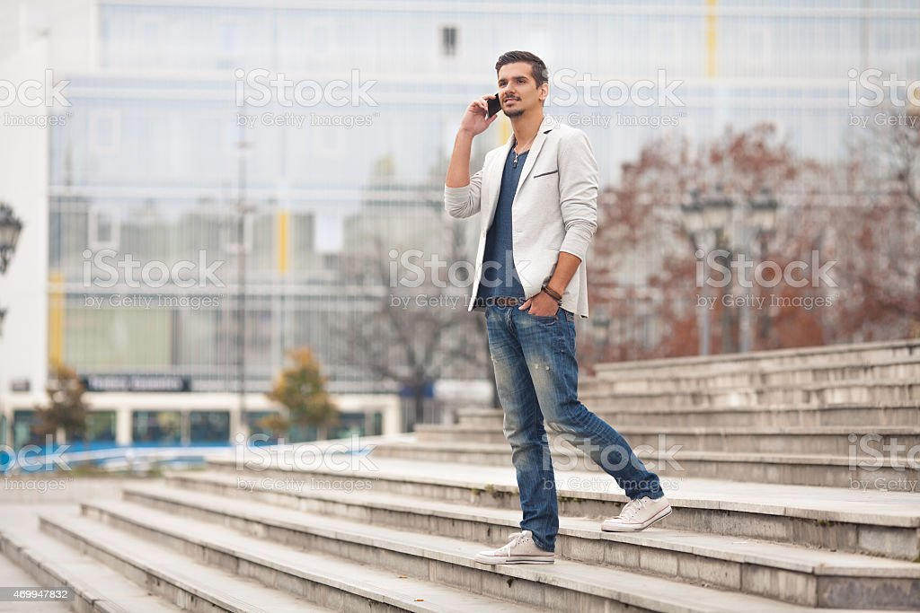 Young man talking on phone while walking down steps outside stock photo