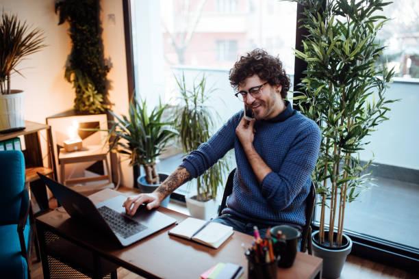 Junger Mann im Telefonat in seinem Heimatbüro – Foto