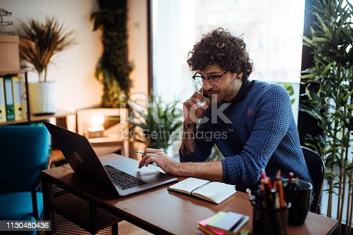 istock Young man talking on the phone in his home office 1130480436