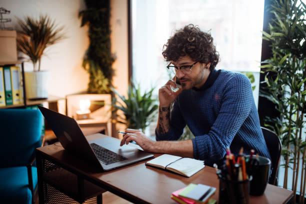 hombre joven hablando por teléfono en su oficina en casa - trabajo freelance fotografías e imágenes de stock