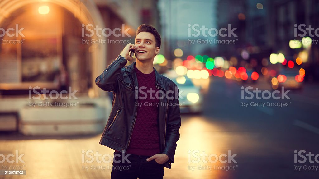 Young man talking on the phone outdoors at nighttime stock photo