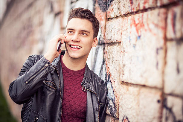 young man talking on the phone outdoors - one young man only stock photos and pictures