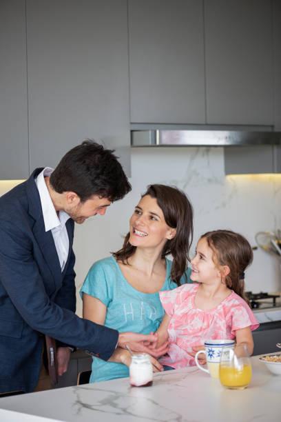 joven hablando con su esposa e hija en el mostrador de la cocina - happy couple sharing a cup of coffee fotografías e imágenes de stock