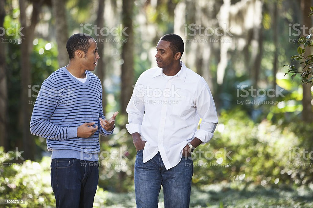 Young man talking with father in park stock photo