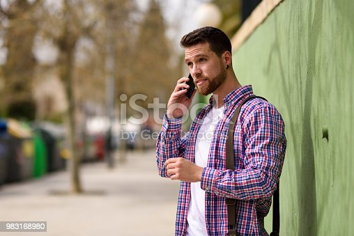 Young man talking with his smart phone in urban background. Guy wearing casual clothes. Lifestyle concept.