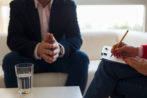 Young man talking with therapist stock photo