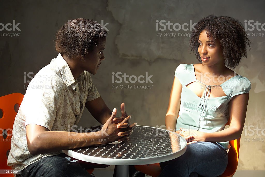 Young Man Talking with Woman and Sitting at Cafe Table stock photo