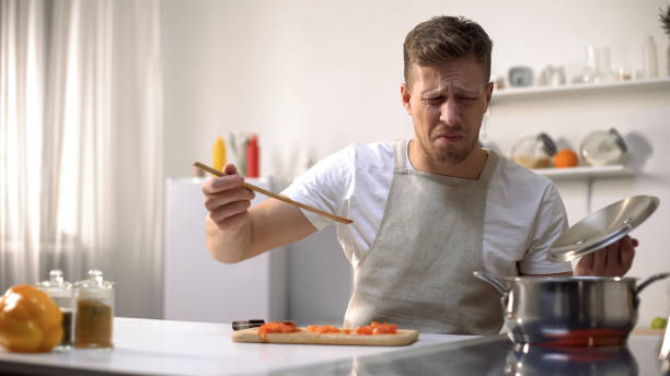young man tasting cooked food with disgusted face expression, funny grimacing - fail cooking imagens e fotografias de stock