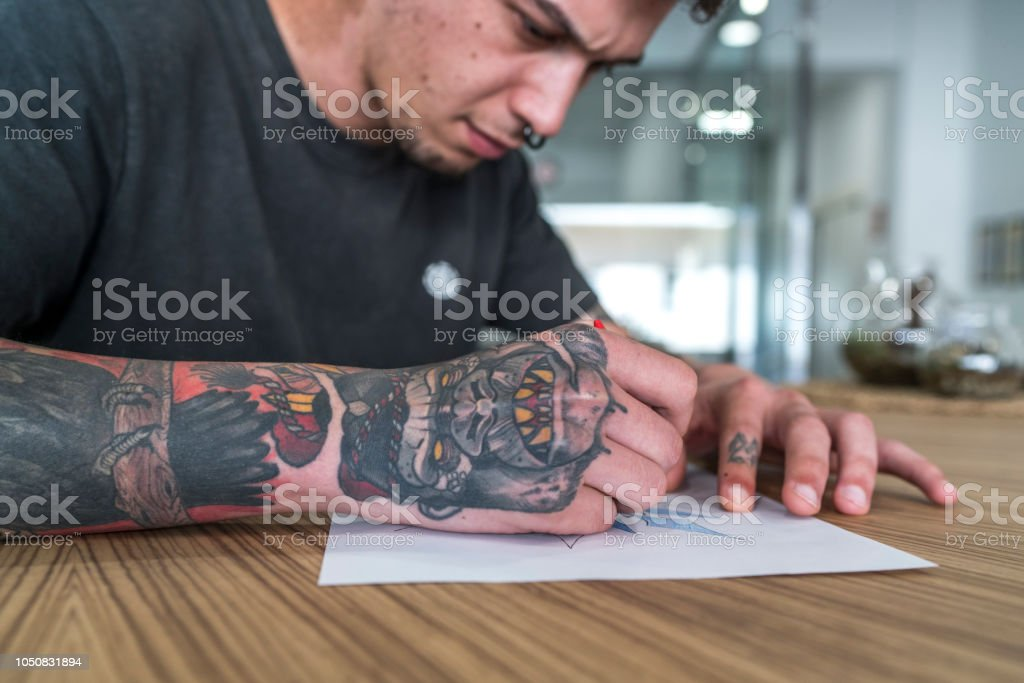 Young man tattooed drawing a tattoo. стоковое фото