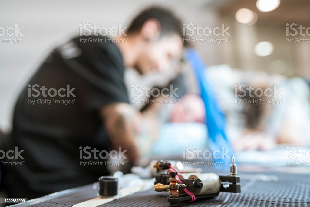 Young man tattooed tattooing a man's head стоковое фото