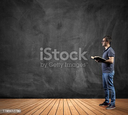 1077234988 istock photo Young man teacher standing holding book looking blank blackboard on domestic room classroom wooden flooring 1193412780
