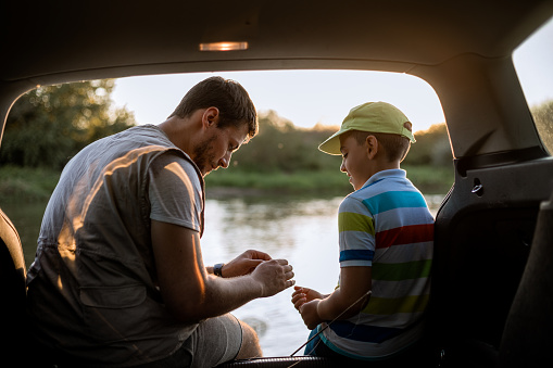Young man teaching a brother how to tie a knot on the fishing line. They are sitting in the back of the car.