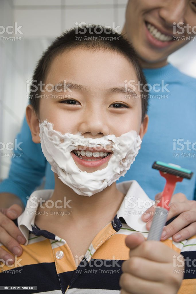 Young man teaching boy (8-9) to shave, smiling foto royalty-free