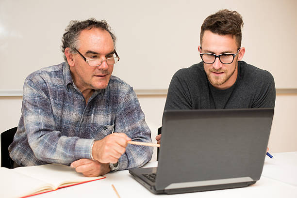 Young man teaching eldery man of usage of computer. stock photo