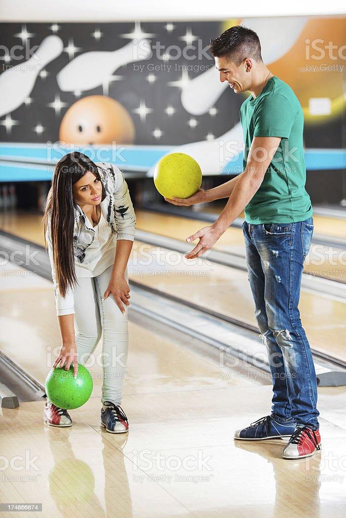 Young man teaching girlfriend bowling. royalty-free stock photo