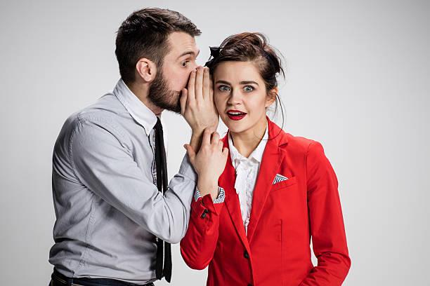 hombre joven contar chismes a su colega en la mujer - cotilleo fotografías e imágenes de stock