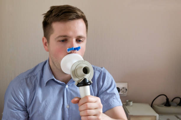 Young man testing breathing function by spirometry stock photo