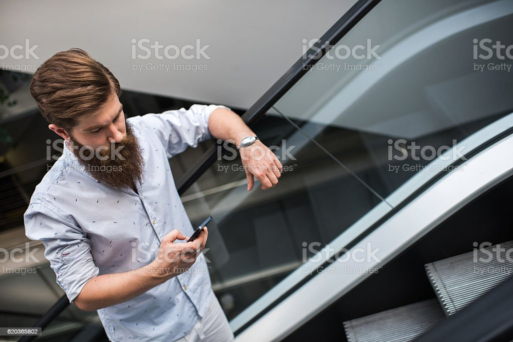 Young man text messaging on mobile phone on escalator. zbiór zdjęć royalty-free