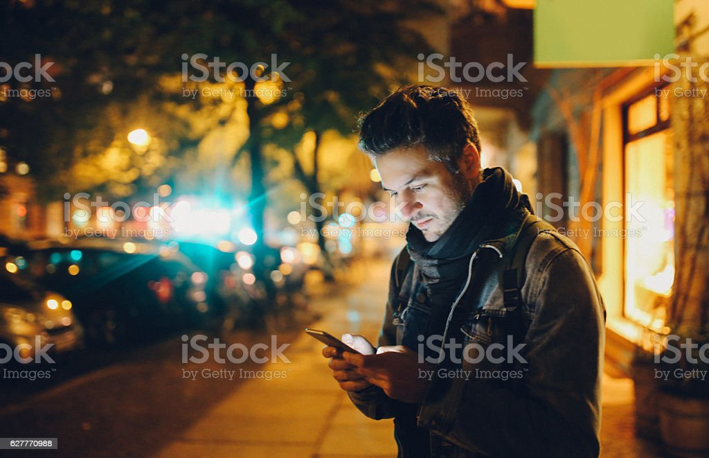 Young man texting in Berlin stock photo