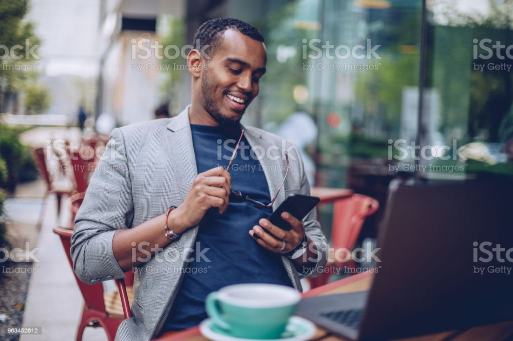 Young man texting in coffee shop - Zbiór zdjęć royalty-free (Afrykanin)